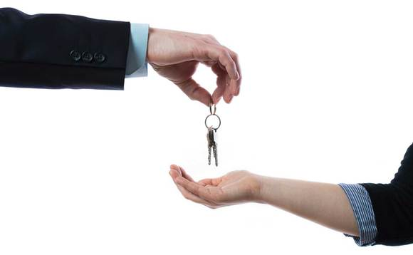 two hands holding keys to house